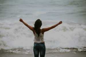 young woman facing away from camera. She is on a grey beach looking out over the water. She has her arms outstretched victoriously because she can finally feel better with teenage therapy. Mountainside Counseling offers teen therapy in new jersey. Contact us today!