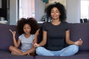 Mindful mom and daughter doing yoga together on the couch. Mindfulness-based therapy in New Jersey is available with a trained mindfulness therapist at Mountainside Counseling near Westfield, NJ. Visit us online in New Jersey for counseling and telehealth.