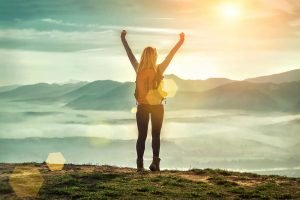 Happy woman with open hands up on the green grass on the peak of mountain. You can feel better after online therapy for depression in New Jersey with Mountainside Counseling's Depression Treatment near Westfield, NJ