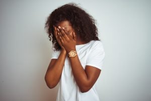 Young african american woman wearing t-shirt standing over isolated white background with sad expression covering face with hands while crying. Depression treatment in Westfield, NJ at Mountainside Counseling or in online therapy for depression in New Jersey