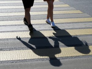 A couple crossing the street at a crosswalk. Female and male feet on a pedestrian crossing, shadows of the people on the street for family addiction counseling in new jersey and online therapy in New jersey with video therapy at Mountainside, NJ counseling center for addiction treatment and family addiction counseling.
