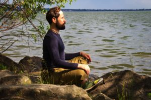 A bearded man is meditating by the river Emotional meditating Lifestyle. Introspection Relaxing Outdoors might need therapy for young adults in New Jersey for anxiety treatment, depression treatment or addiction counseling. Therapy for millennials in New Jersey can happen with Nicole at Mountainside Counseling or in online therapy in New Jersey 07092 & 07090