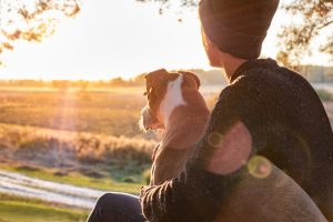 Hugging a dog in beautiful nature at sunset for couples therapy with Nicole Locorriere, LMFT for couples on the brink of divorce in Mountainside, NJ. You can get discernment counseling in New Jersey with marriage counseling in Westfield, NJ at Mountainside Counseling Center in NJ 07092 & 07090