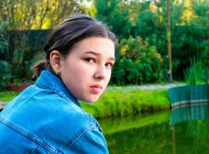 close up picture of a teen looking over her shoulder towards the camera. She is in a green park, with a pond behind her. She is having trouble overcoming her anxiety. Teen therapy in new jersey is possible at Mountainside Counseling Center. Zip 07092 & 07090