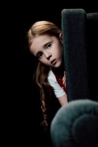 anxious child looking at camera while hiding behind armchair while her parents are fighting. Read on about the worst advice for couples in New Jersey from discernment counseling and marriage counselor from Mountainside, NJ. You can get help with online therapy in New Jersey here.